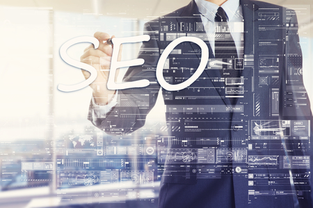 The businessman in the office is writing on the banner board: SEO