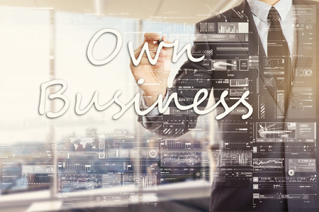 the businessman in the office is writing on the transparent board: Own Business Stock Photo