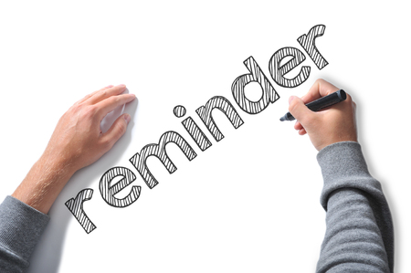 implication: Hand writing reminder word on a white sheet of paper