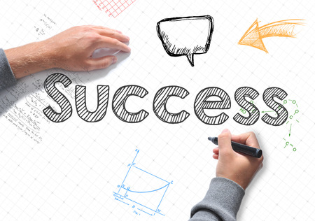 Hand writing Success word on a white sheet of paper Stock Photo