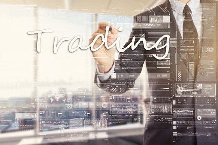 trading board: the businessman in the office is writing on the transparent board: Trading Stock Photo