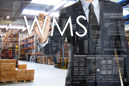 The businessman is writing things connected with the logistics in warehouse. WMS Standard-Bild