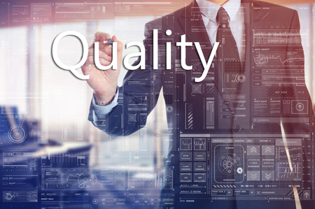 stock certificate: the businessman in the office is writing on the transparent board words associated with the manufacturing: Quality