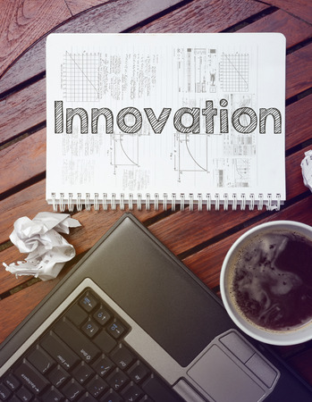 work place - table with notebook with note about: innovation