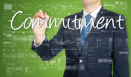 business man writing commitment on green background