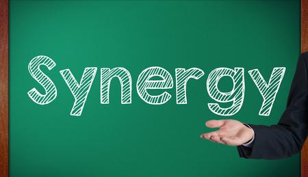 Synergy on a blackboard presenting on blackboard by hand