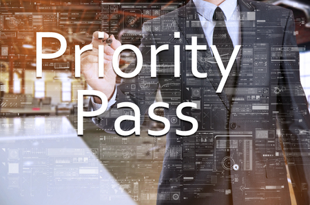 relevance: the businessman in the office is writing on the transparent board: Priority Pass Stock Photo