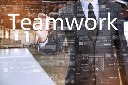 harmonize: the businessman in the office is writing on the transparent board: Teamwork Stock Photo