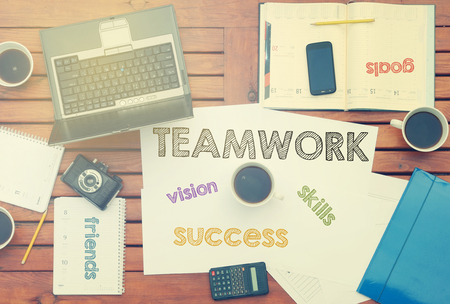 work place with notebook with note about: Teamwork with laptop and coffee on table Stock Photo