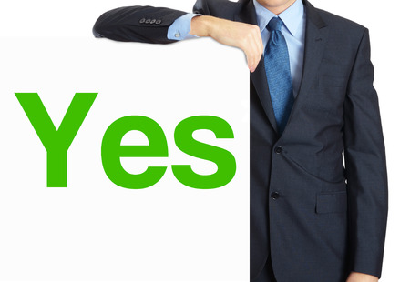 Businessman holding or showing banner with text Yes Stock Photo