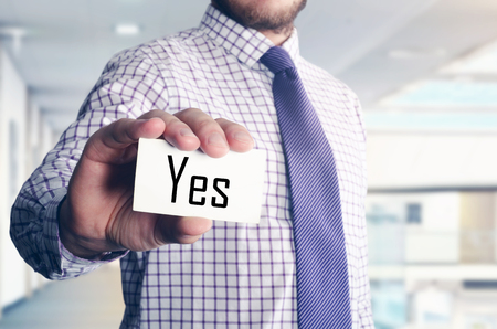businessman in office showing card with text: Yes
