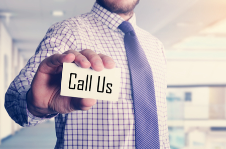 businessman in office showing card with text: Call Us