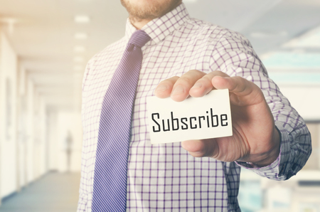 businessman in office showing card with text: Subscribe