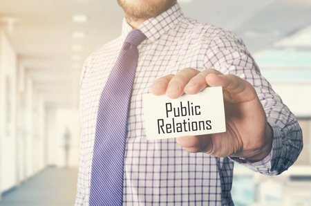 businessman in office showing card with text: Public Relations