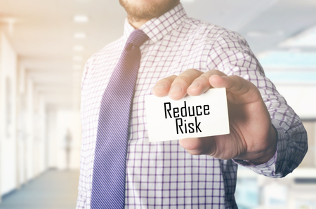 businessman in office showing card with text: Reduce Risk 版權商用圖片