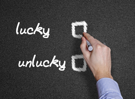 lucky and unlucky handwritten with white chalk black background or blackboard