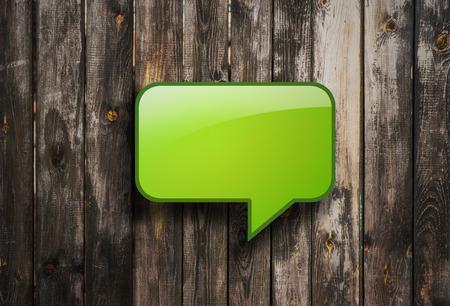 green bubble speech on wooden background