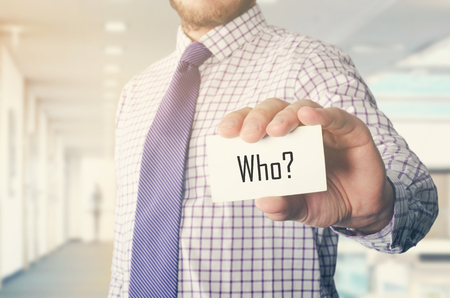businessman in office showing card with text: Who ?