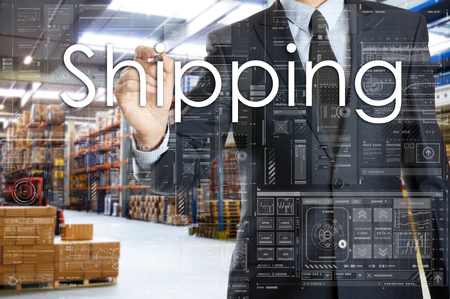 the businessman is writing things connected with the logistics in warehouse. Shipping