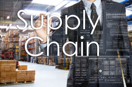 the businessman is writing things connected with the logistics in warehouse. Supply Chain