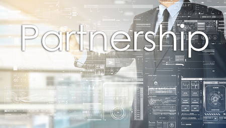 the businessman in the office is writing on the transparent board: Partnership Stock Photo