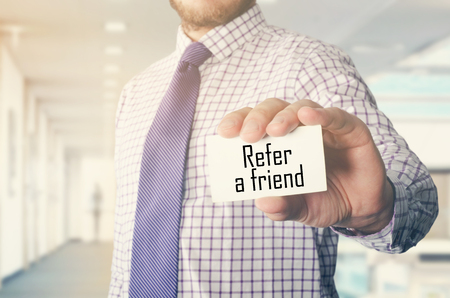 businessman in office showing card with text: Refer a friend