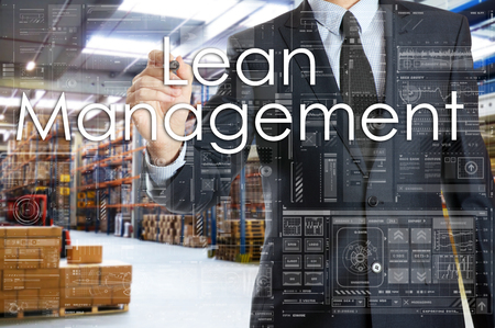 the businessman is writing things connected with the logistics in warehouse. Lean Management