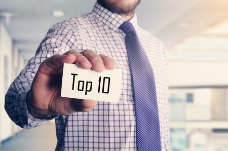 businessman in office showing card with text: Top 10