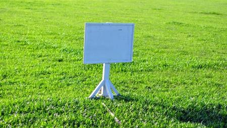 a single sign board on fresh green field photo