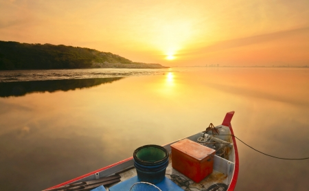 the lonely fisherman boat during sunrise photo