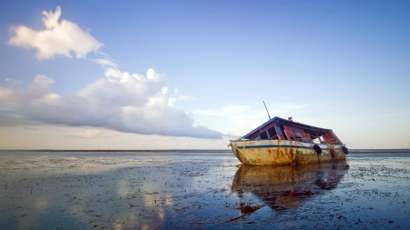 old abandoned ship left alone on the seaside and blue sky as a background photo
