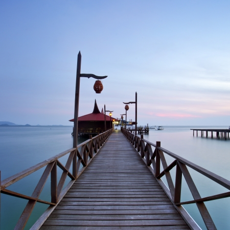 wooden jetty on mabul island looking across the ocean to sipadan island photo