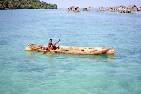 celebes: MABUL ISLAND, SABAH, MALAYSIA - MARCH 3: local sea gypsy kid paddles a boat March 3, 2013 in Mabul Island, Sabah, Malaysia. Children live here do not attend school for lack of means and resources