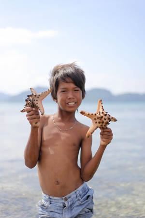 MABUL ISLAND, SABAH, MALAYSIA - MARCH 3: Local sea gypsy kid hold a starfish March 3, 2013 in Mabul Island, Sabah, Malaysia. Children live here do not attend school for lack of means and resources
