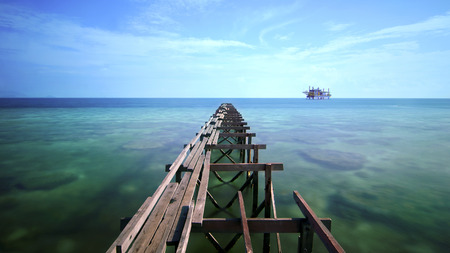 view of old broken jetty during sunny day with coral and green sea water in long exposure. noise may visible due to long exposure and high iso photo