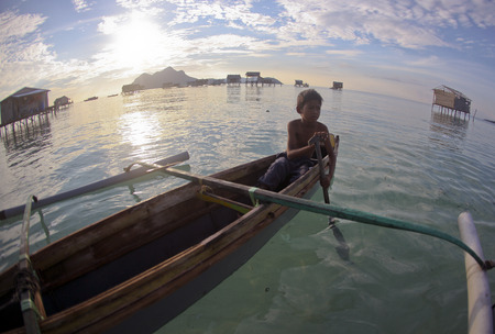 SIBUAN ISLAND, SABAH, MALAYSIA - MARCH 03 : Unidentified Sea Gypsies boy paddles a boat on March 03, 2014 in Sabah, Malaysia. The Sea Gypsies are sea nomads that move from one place to another.