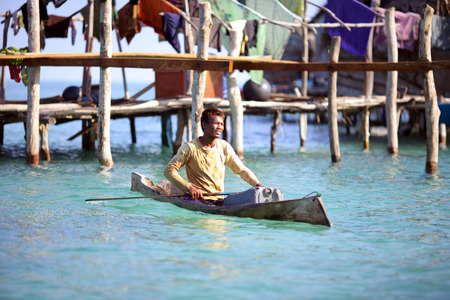 MABUL ISLAND, SABAH, MALAYSIA - MARCH 03 : Unidentified Sea Gypsies boy paddles a boat on March 03, 2014 in Sabah, Malaysia. The Sea Gypsies are sea nomads that move from one place to another.
