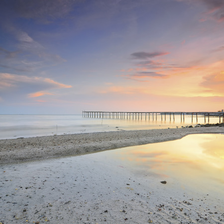 Beautiful vibrant  sunset over abandoned pier and building at sea. photo