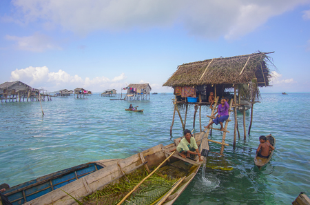 lived here: SABAH, MALAYSIA - APR 19: Unidentified Bajau Laut kids on a boat in Bodgaya Island on August 19, 2015. They lived in a house built on stilts in the middle of sea, boat is the main transportation here.