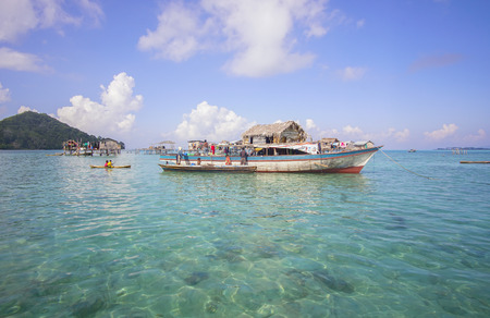 lived here: SABAH, MALAYSIA - APR 19: Unidentified Bajau Laut kids on a boat in Bodgaya Island on August 19, 2015. They lived in a house built on stilts in the middle of sea, boat is the main transportation here