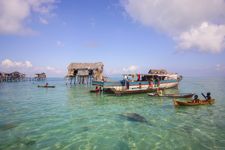 inhabit: SABAH, MALAYSIA - APRIL 19: Unidentified Bajau Laut kids on a boat in Maiga Island on April 19, 2015. They inhabit villages built on stilts in the middle of sea, boat is the main transportation here.