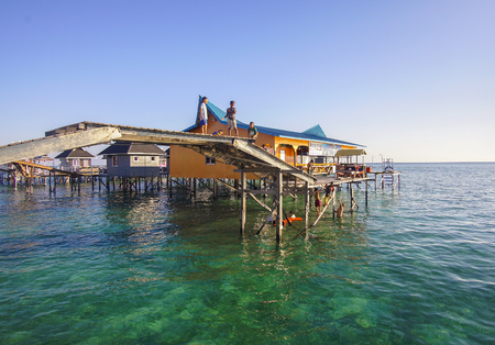 inhabit: SABAH, MALAYSIA - NOVEMBER 19: Unidentified Bajau Laut kids playing on the bridge on November 19, 2015. They inhabit villages built on stilts in the middle of sea, boat is the main transportation here. Editorial