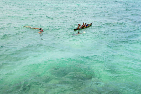inhabit: SABAH, MALAYSIA - NOVEMBER 19: Unidentified Bajau Laut kids on a boat in Maiga Island on November 19, 2015. They inhabit villages built on stilts in the middle of sea, boat is the main transportation here.