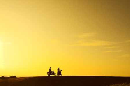 sea scape: silhoutte of a man standing with his bike during beautiful golden sunrise.