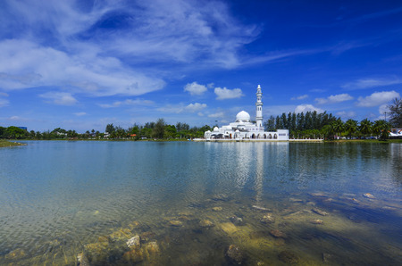 islam: Beautiful white mosque with reflection in the lake during clean blue sky.