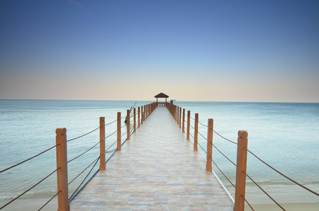 tropica: long pier heading to the sea under the beautiful blue sky