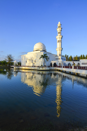 int: Beautiful white mosque with reflection int he lake during clean blue sky
