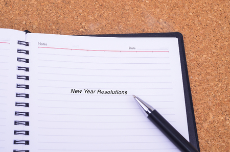 personal decisions: A pen and notebook written New Year Resolution on a wooden table with copyspace area