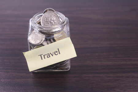 space   area: Finacial concept. Money in the glass on wooden table with Travel word and copy space area. Stock Photo