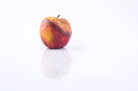 uneatable: Wilted rotten apple isolated on white background.